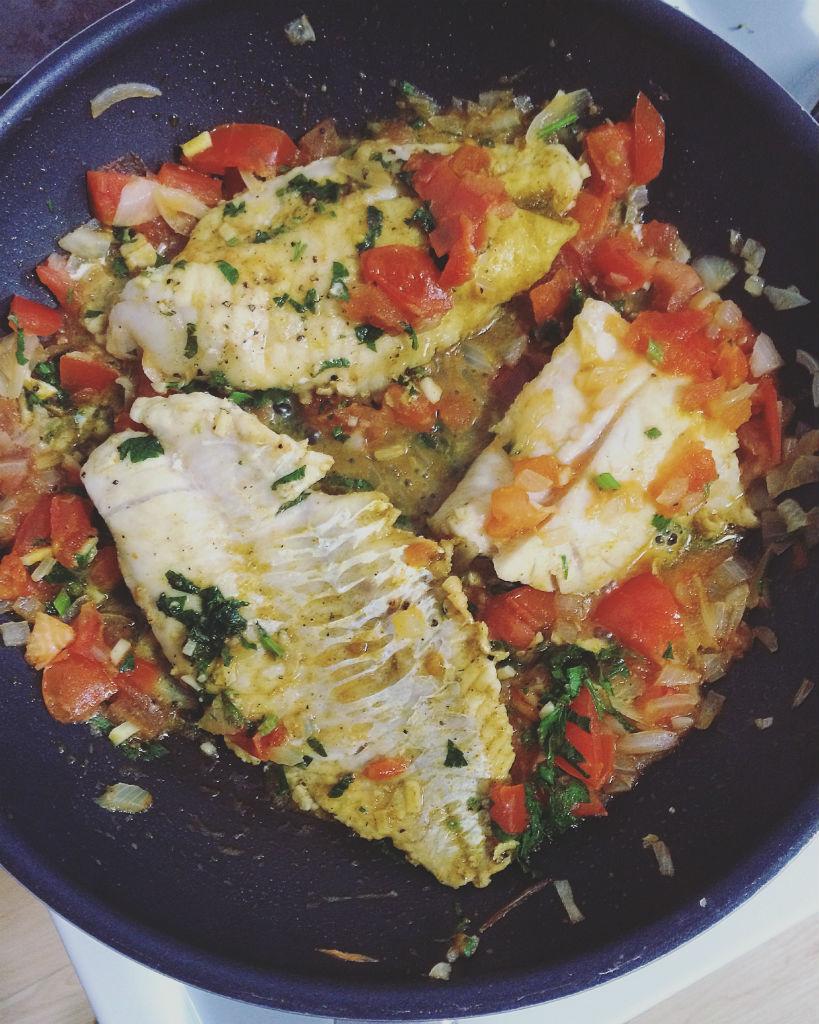 Rotbarsch in fruchtigem Curry-Tomaten-Sud. Zubereitung in der Pfanne.