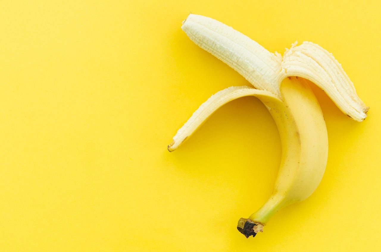 Gelbe Banane mit Schale halb gepellt